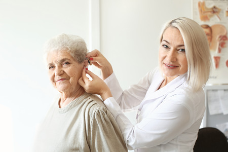 Otolaryngologist putting hearing aid in senior woman's ear indoors