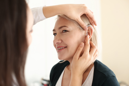 Otolaryngologist putting hearing aid in womans ear on light background Stock Photo