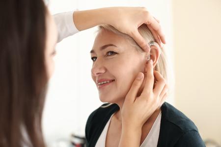 Otorrinolaringólogo poniendo audífonos en el oído de la mujer sobre fondo claro Foto de archivo