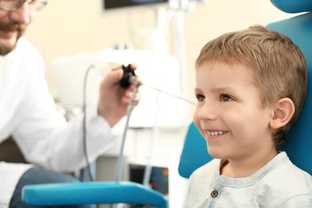 Otolaryngologist examining little boy's ear with ENT telescope in hospital