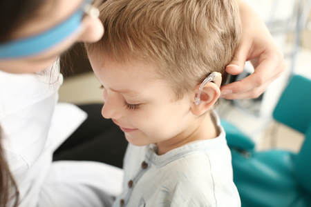 Otolaryngologist putting hearing aid in little boys ear indoors