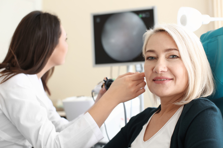 Mature woman in otolaryngologists office Stock Photo