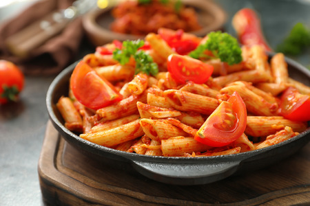 Frying pan with tasty penne pasta and tomato sauce on table, closeup