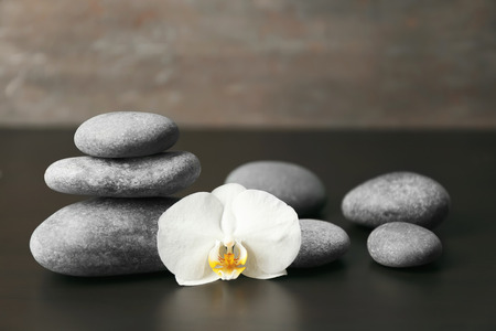 Spa stones and beautiful orchid flower on dark table