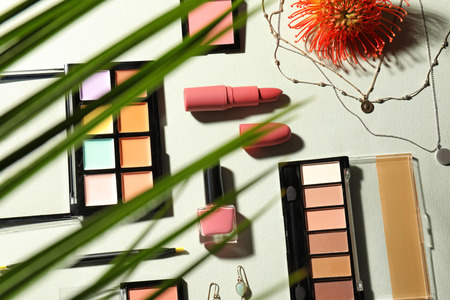 View at set of decorative cosmetics and accessories through tropical leaf, on light background