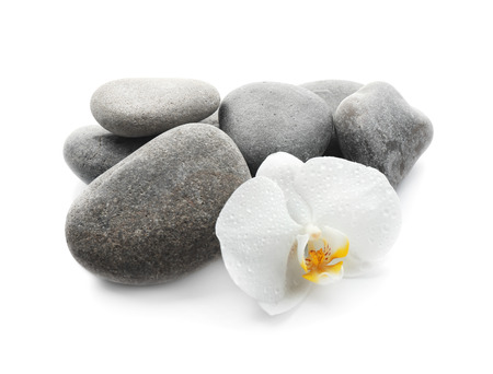 Spa stones and beautiful orchid flower on white background Stockfoto