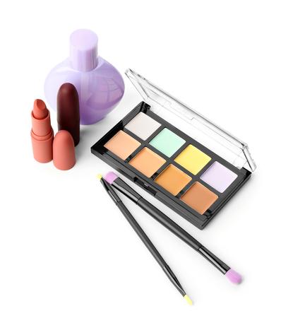 Set of decorative cosmetics with brushes on white background