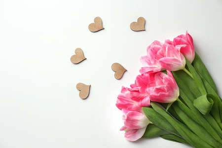 Beautiful tulips and small decorative hearts on white background