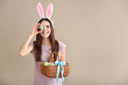 Beautiful young woman with Easter eggs and bunny ears on color background Stock Photo