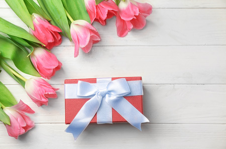 Beautiful tulips and gift box on white wooden background, top view