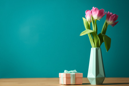 Vase with beautiful tulips and gift box on table against color background
