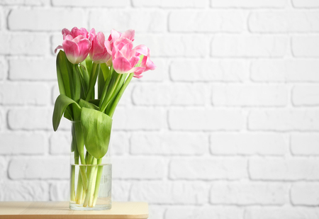 Vase with beautiful tulips against white brick wall