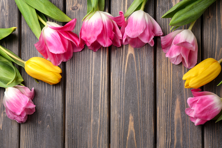 Beautiful fresh tulips on wooden background, top view