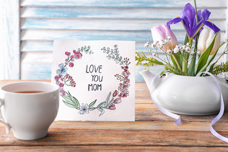 Card with words LOVE YOU MOM, cup of tea and flowers on table. Mother's day celebration Archivio Fotografico