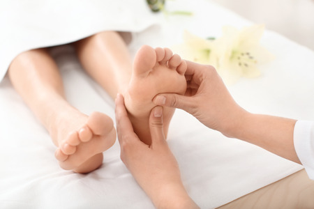 Young woman enjoying foot massage in spa salon, focus on legs