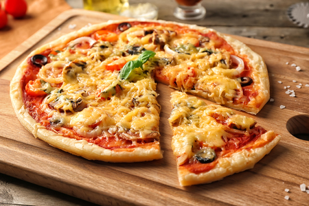 Tasty pizza on wooden board, closeup Фото со стока