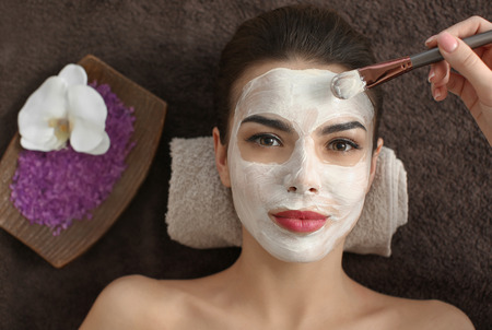Cosmetologist applying mask on young woman's face in spa salon 免版税图像