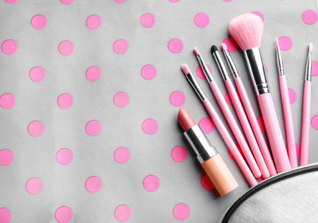 Cosmetic bag with different brushes of professional makeup artist and lipstick on color background