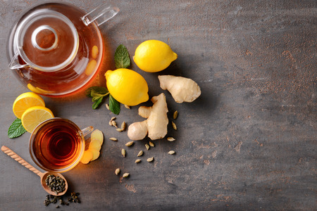 Flat lay composition with cup of hot tea, lemon and ginger on table Stok Fotoğraf