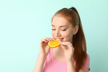 Beautiful young woman eating citrus fruit on color background