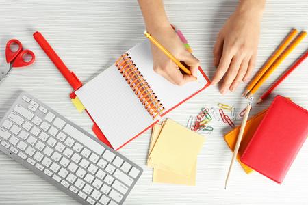 Frau schreibt im Notizbuch am Tisch, Ansicht von oben. Arbeitsplatzzusammensetzung