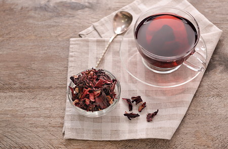 Bowl with dry hibiscus tea and cup of aromatic drink on wooden table