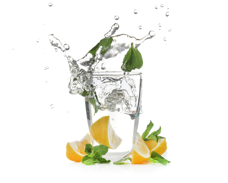 Glass with splashing water and sliced citrus fruit on white background