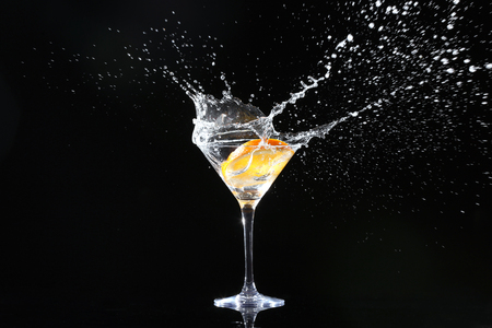 Glass with splashing cocktail and slice of orange on black background Foto de archivo