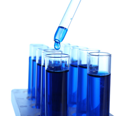 Dripping blue liquid into test tubes on white background Stock Photo