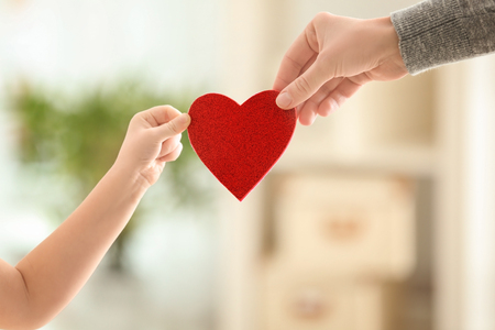 Hands of little girl and her mother holding red heart against blurred background