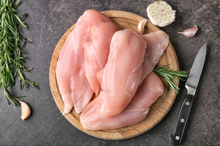 Raw chicken fillet on wooden board Stockfoto