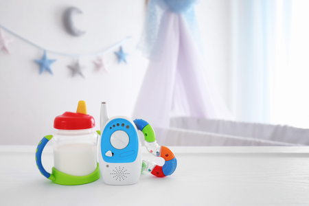 Baby monitor, rattle and sippy cup on table in room. Radio nanny