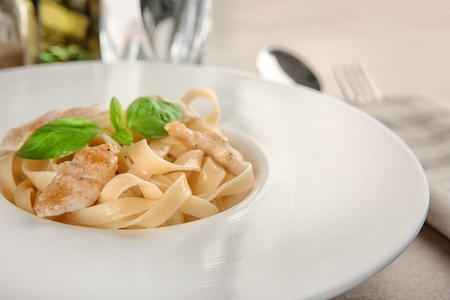 Plate of delicious pasta with chicken fillet, closeup