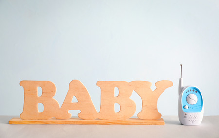 Baby monitor and wooden letters on table against color background 版權商用圖片