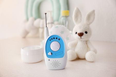 Baby monitor and different accessories on table. Radio nanny