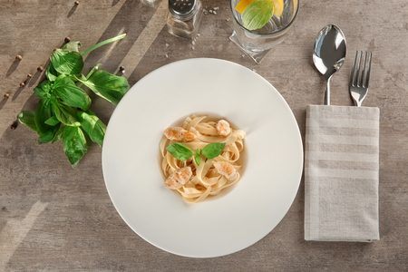 Plate of delicious pasta with chicken fillet on table, top view
