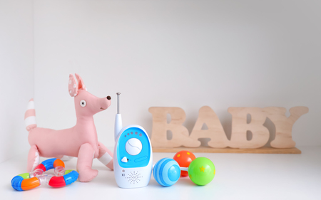 Baby monitor and toys on shelf
