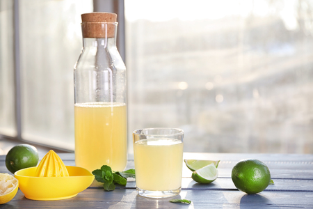 Fresh citrus drink in glassware and lime on table Stockfoto