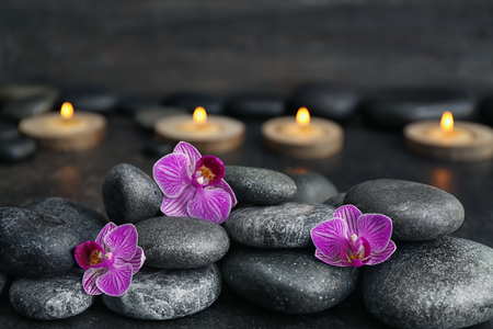 Spa stones and beautiful orchid flowers on dark background