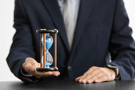 Man holding hourglass over table. Time management concept Banque d'images