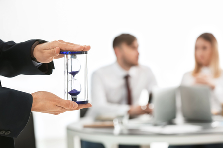 Man holding hourglass and blurred people on background. Time management concept Stock Photo