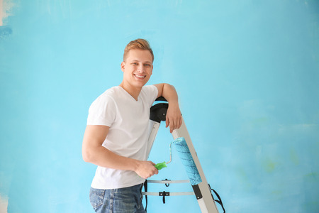 Young male painter with roller standing on ladder against color background
