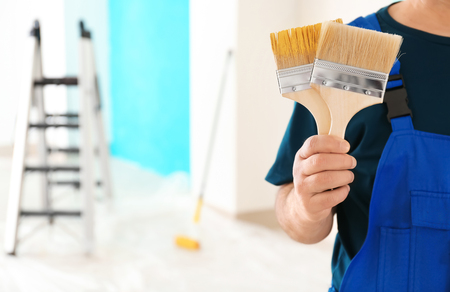 Male painter in uniform with brushes indoors