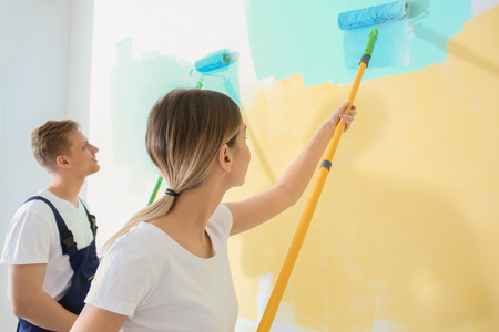Young painters using rollers for refurbishing color of wall indoors