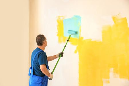 Male painter in uniform working indoors Reklamní fotografie