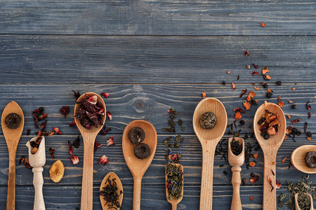 Spoons with different types of dry tea leaves on wooden background