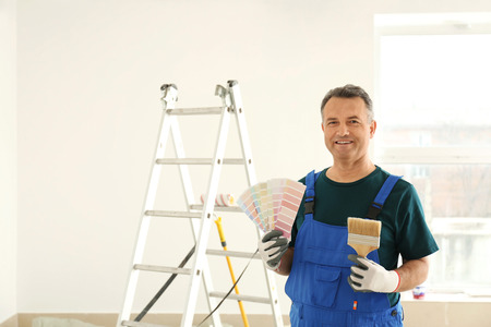 Male painter in uniform with color palette samples and brush indoors