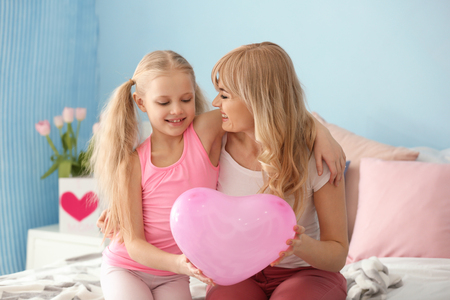 Portrait of cute little girl and her mother with balloon at home