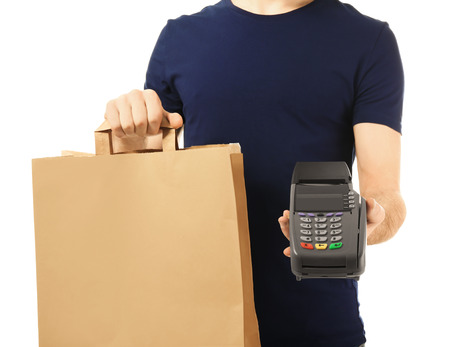 Delivery man holding paper bag with food and payment terminal on white background
