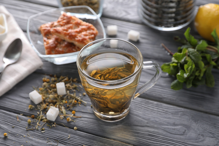 Glass cup with herbal tea on table Imagens